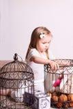 Маленькая милая белокурая девушка сидя в комнате и играя с игрушками и Стоковое фото RF