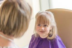 Маленькая милая белокурая девушка усмехается и смотрится парикмахер во время процесса стрижки Стоковая Фотография RF