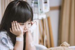Маленькая милая девушка в больнице сидит на терпеливой кровати для того чтобы ждать Стоковые Изображения RF