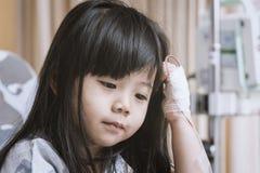 Маленькая милая девушка в больнице сидит на терпеливой кровати для того чтобы ждать Стоковые Фото