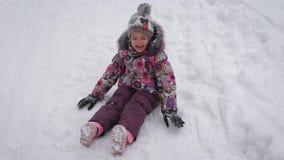 Маленькая милая девушка в теплых одеждах сидит на снеге и плакать Малая принцесса идя снаружи в playi зимы акции видеоматериалы
