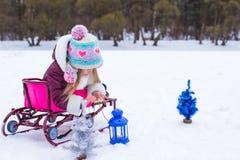 Маленькая милая девушка греет ее руки на свече в сини Стоковая Фотография