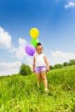 Маленькая милая девушка держа 3 воздушного шара летая Стоковая Фотография