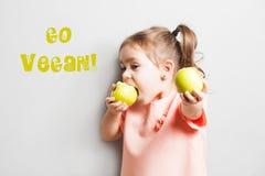 Маленькая милая девушка есть яблоко надпись идет Vegan Стоковое Изображение RF