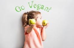 Маленькая милая девушка есть яблоко надпись идет Vegan Стоковое фото RF