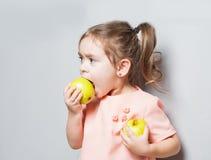 Маленькая милая девушка есть яблоко надпись идет Vegan Стоковые Фотографии RF