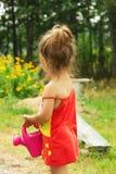 Маленькая милая девушка играя с чонсервной банкой завода моча Стоковые Фото