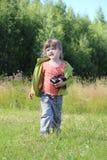 Маленькая милая девушка идет с камерой среди зеленой травы Стоковое Изображение
