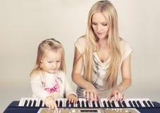 маленькая милая девушка при ее мама играя на синтезаторе стоковое фото