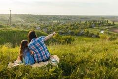 Маленькая милая девушка при ее мать сидя на заходе солнца Стоковая Фотография