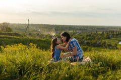 Маленькая милая девушка при ее мать сидя на заходе солнца Стоковые Фото