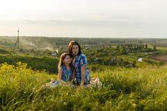 Маленькая милая девушка при ее мать сидя на заходе солнца Стоковые Фотографии RF