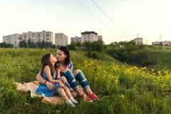 Маленькая милая девушка при ее мать сидя на заходе солнца Стоковое Изображение