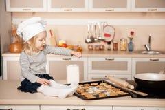 Маленькая милая девушка при шляпа шеф-повара подготавливая печенья Стоковое Фото