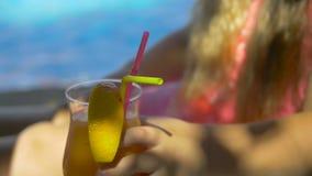 Маленькая милая девушка сидя в стуле около бассейна принимая стекло свежего апельсинового сока Милый ребенк наслаждаясь ей сток-видео