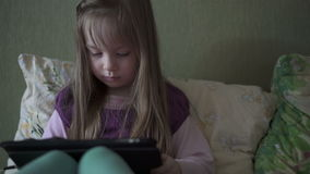 Маленькая милая девушка сидя на софе и играя с таблеткой акции видеоматериалы