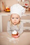 Маленькая милая девушка с тортом удерживания шляпы шеф-повара Стоковая Фотография RF