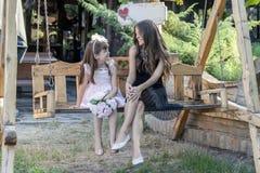 Маленькая милая маленькая девочка и ее мать сидят на стенде и говорят Стоковые Изображения RF