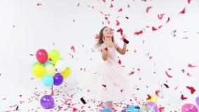Маленькая очаровательная курчавая девушка в чудесном розовом платье с цветками в волосах Прелестная маленькая девочка имеет потех акции видеоматериалы