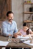 Маленькая дочь и его картина отца с акварелями Стоковые Фотографии RF