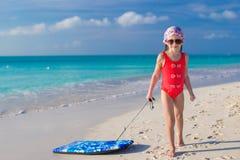 Маленькая прелестная девушка вытягивает surfboard на белизне Стоковое фото RF