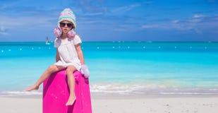 Маленькая прелестная девушка в теплых шляпе и mittens зимы на тропическом пляже Стоковые Изображения