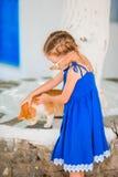 Маленькая прелестная девушка играя с котом имбиря в греческой деревне внешней Стоковое Фото