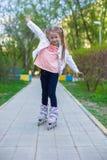 Маленькая прелестная девушка на коньках ролика в парке Стоковые Фото