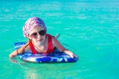 Маленькая прелестная девушка на surfboard в бирюзе Стоковые Изображения