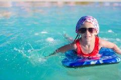 Маленькая прелестная девушка на surfboard в бирюзе Стоковое Изображение RF