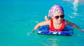 Маленькая прелестная девушка на surfboard в Стоковые Изображения