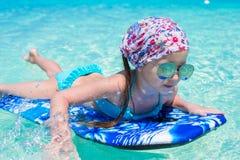 Маленькая прелестная девушка на surfboard в Стоковое Изображение RF