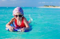 Маленькая прелестная девушка на surfboard в Стоковое Изображение