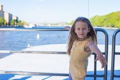 Маленькая прелестная девушка ослабляя на роскошном плавании корабля в большом городе Стоковые Изображения RF
