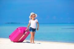 Маленькая прелестная девушка с большим чемоданом на тропическом Стоковые Изображения RF