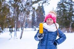 Маленькая прелестная девушка с сладостной мозолью на зиме Стоковое фото RF
