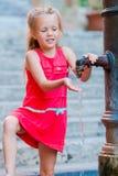Маленькая прелестная питьевая вода девушки от крана снаружи на горячем летнем дне в Риме, Италии Стоковые Фотографии RF