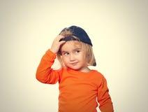 Маленькая смешная девушка в блузке бейсбольной кепки и апельсина Стоковые Фотографии RF