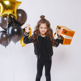 Маленькая современная девушка битника в одеждах моды стоит близко воздушные шары и держит золото присутствующий День рождения стоковые фотографии rf