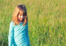 Маленькая счастливая белокурая девушка идя на луг на солнечной весне Стоковые Фотографии RF