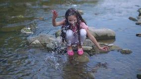 Маленькая счастливая девушка играет около реки Squirting вода на камере сток-видео