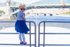 Маленькая счастливая девушка ослабляя на роскошном плавании корабля в большом городе Стоковая Фотография