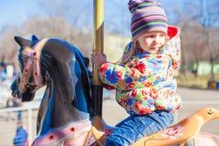 Маленькая счастливая езда девушки на carousel на парке атракционов Стоковые Фотографии RF