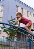 Маленькая усмехаясь девушка используя спортивный инвентарь в спортивной площадке house& x27 квартиры; двор суда s Стоковые Фото
