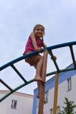 Маленькая усмехаясь девушка используя спортивный инвентарь в спортивной площадке house& x27 квартиры; двор суда s Стоковые Фотографии RF
