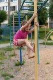 Маленькая усмехаясь девушка используя спортивный инвентарь в спортивной площадке house& x27 квартиры; двор суда s Стоковая Фотография