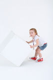 Маленькая удивленная девушка с медалью на комоде обращает куб Стоковые Изображения