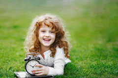 Маленькая школьница отдыхая на лужайке в парке осени Стоковая Фотография RF