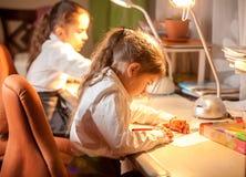Маленькая школьница сидя за таблицей и рисовать стоковые фотографии rf