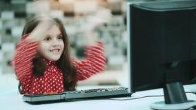 Маленькая школьница с темными волосами и блузкой с точками польки, компьютером надомного труда, печатая текстом акции видеоматериалы